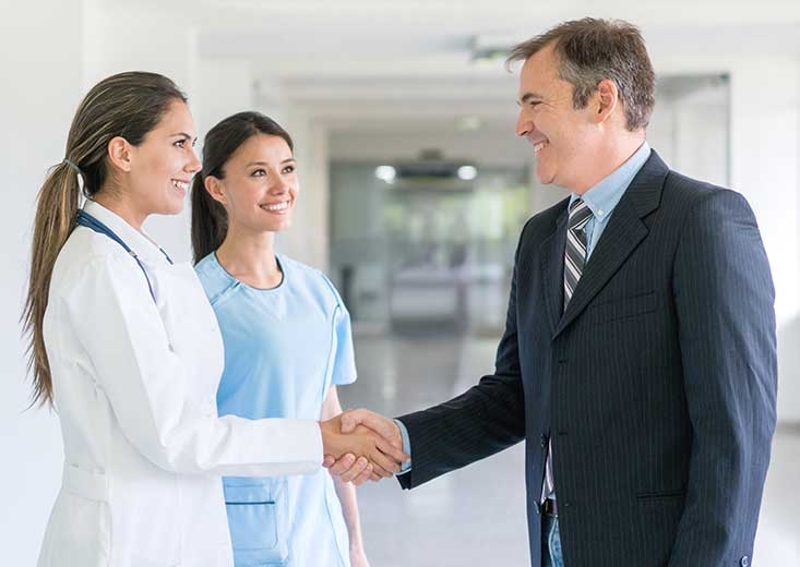 A Health Administration Certificate online student shakes hands with a doctor and nurse.