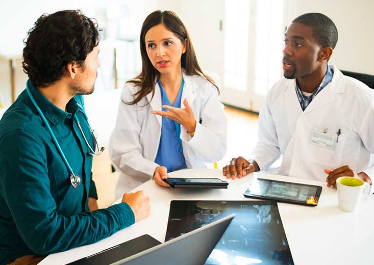 Two Master's in Health Informatics online students discuss patient files with a doctor on their tablets and laptop.